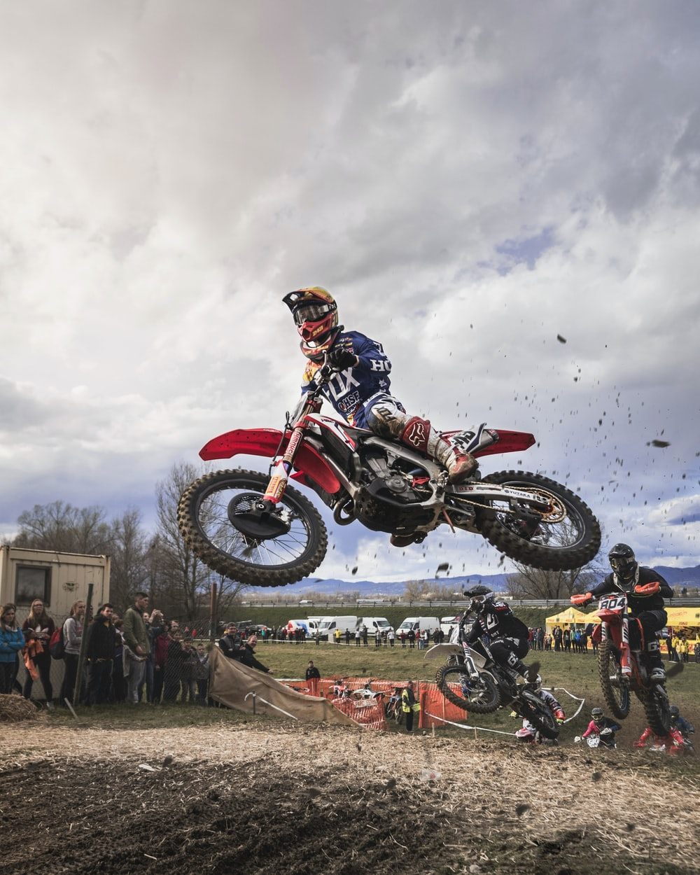 man riding red motocross dirt bike