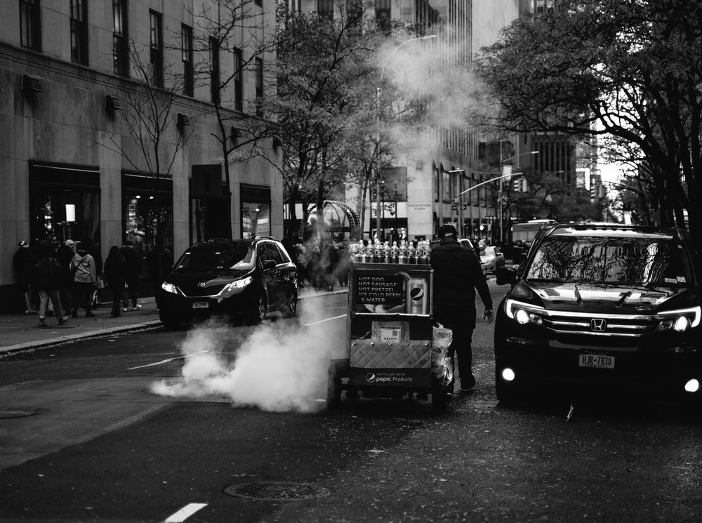 grayscale photography of vehicles on road