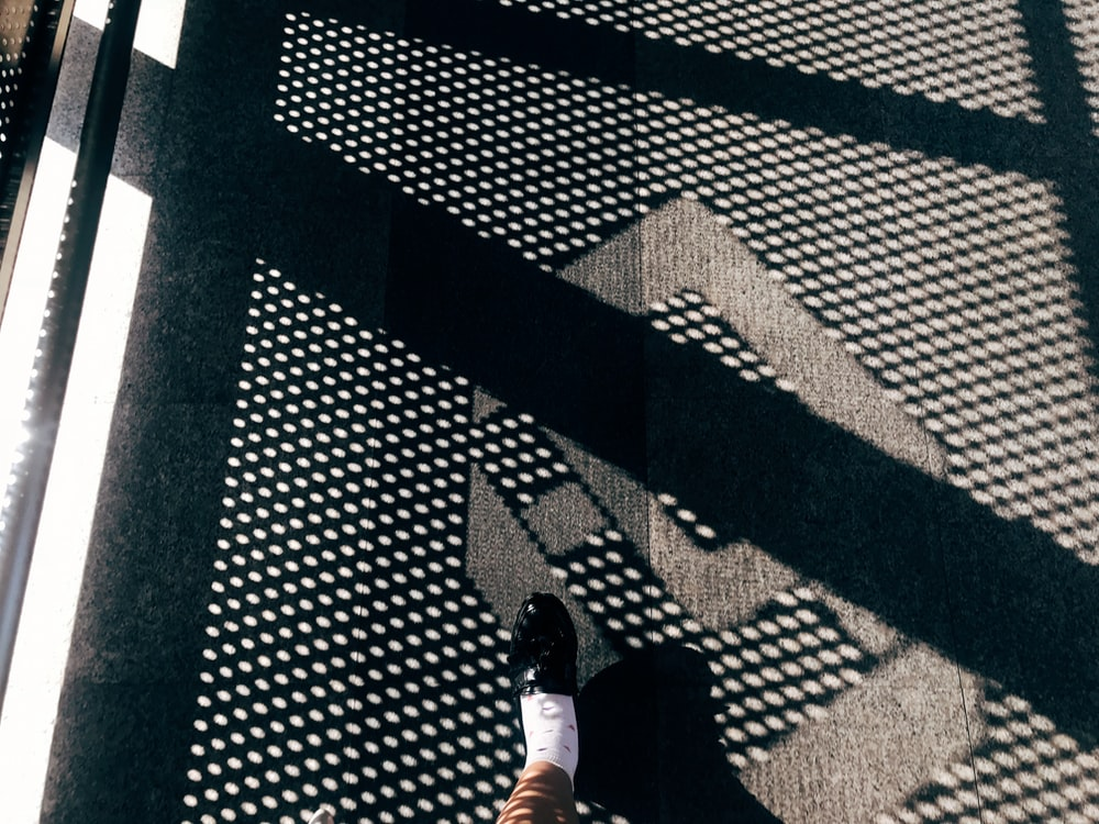 person wearing unpaired black shoe during daytime