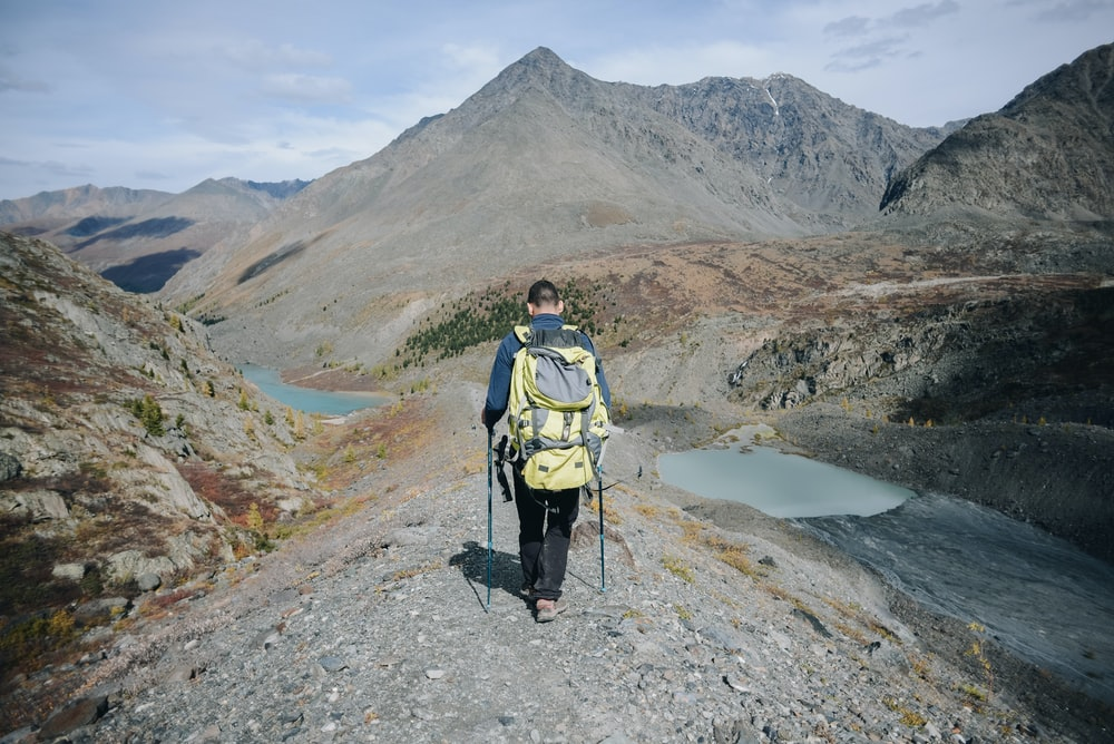 man walking toward mountains during during daytime