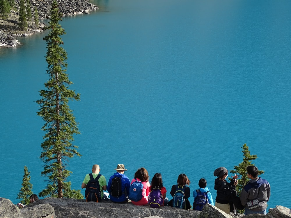 people sitting on rock edge facing body of water
