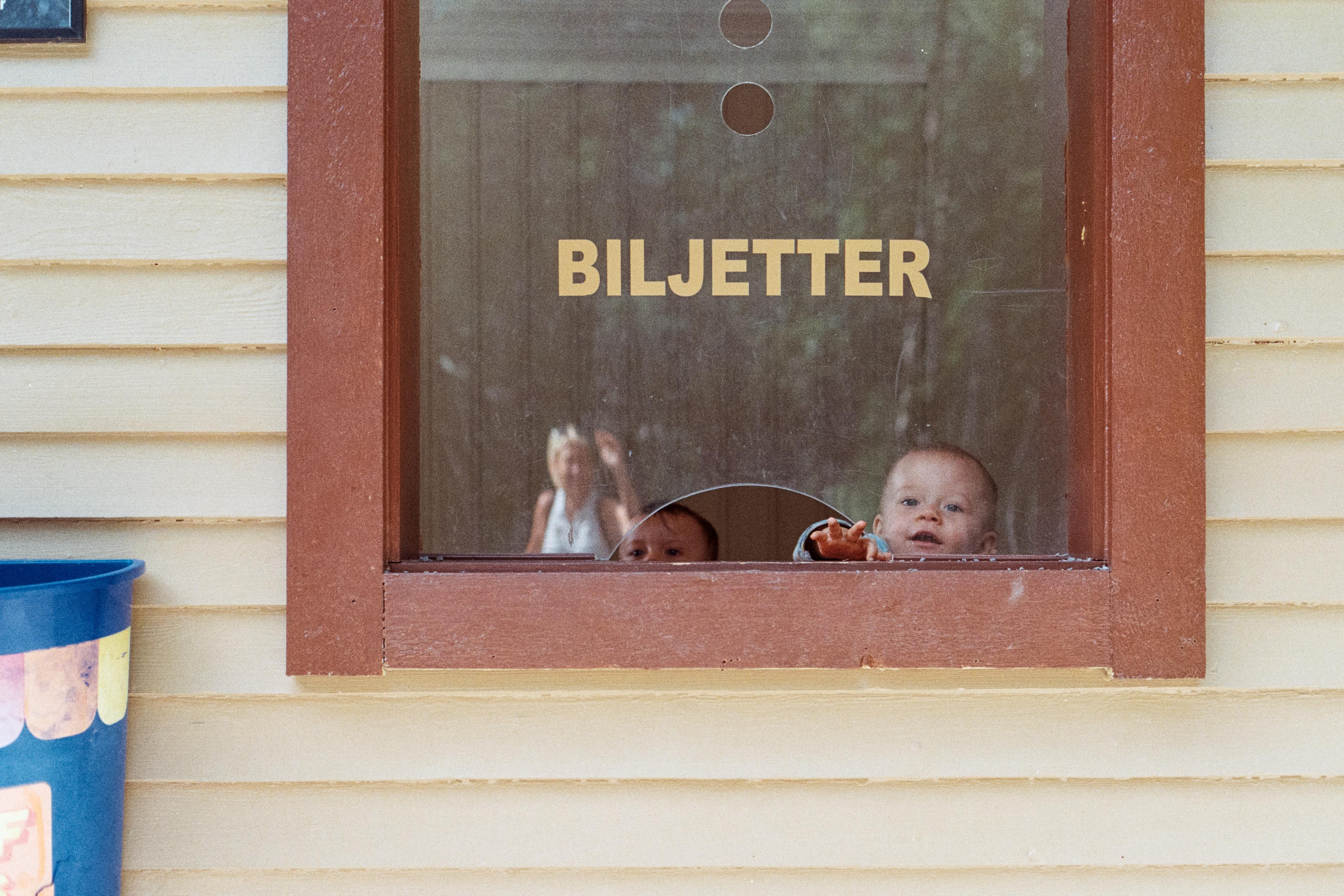 two babies near glass window