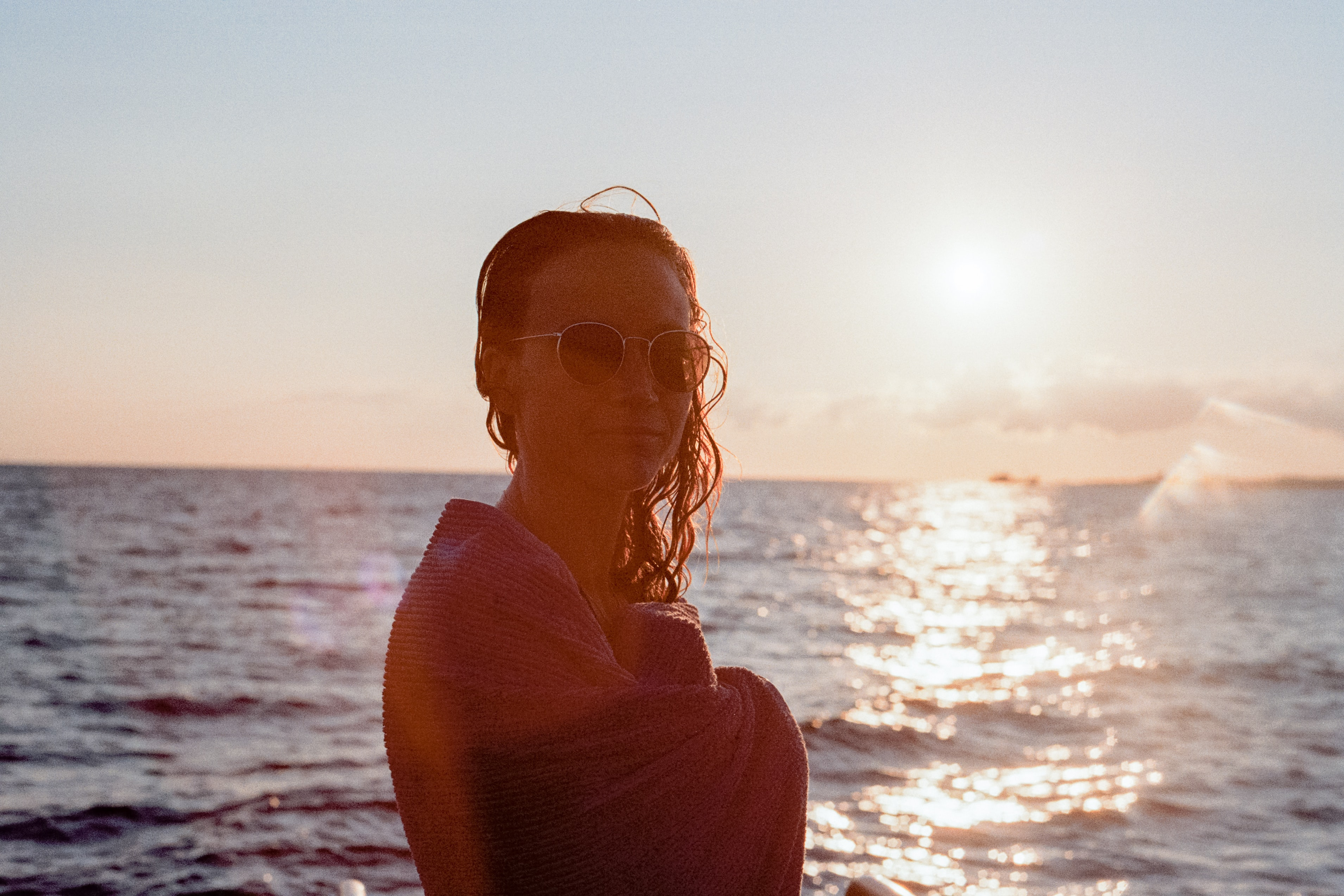 woman wearing sunglasses smiling at the beach during golden hour
