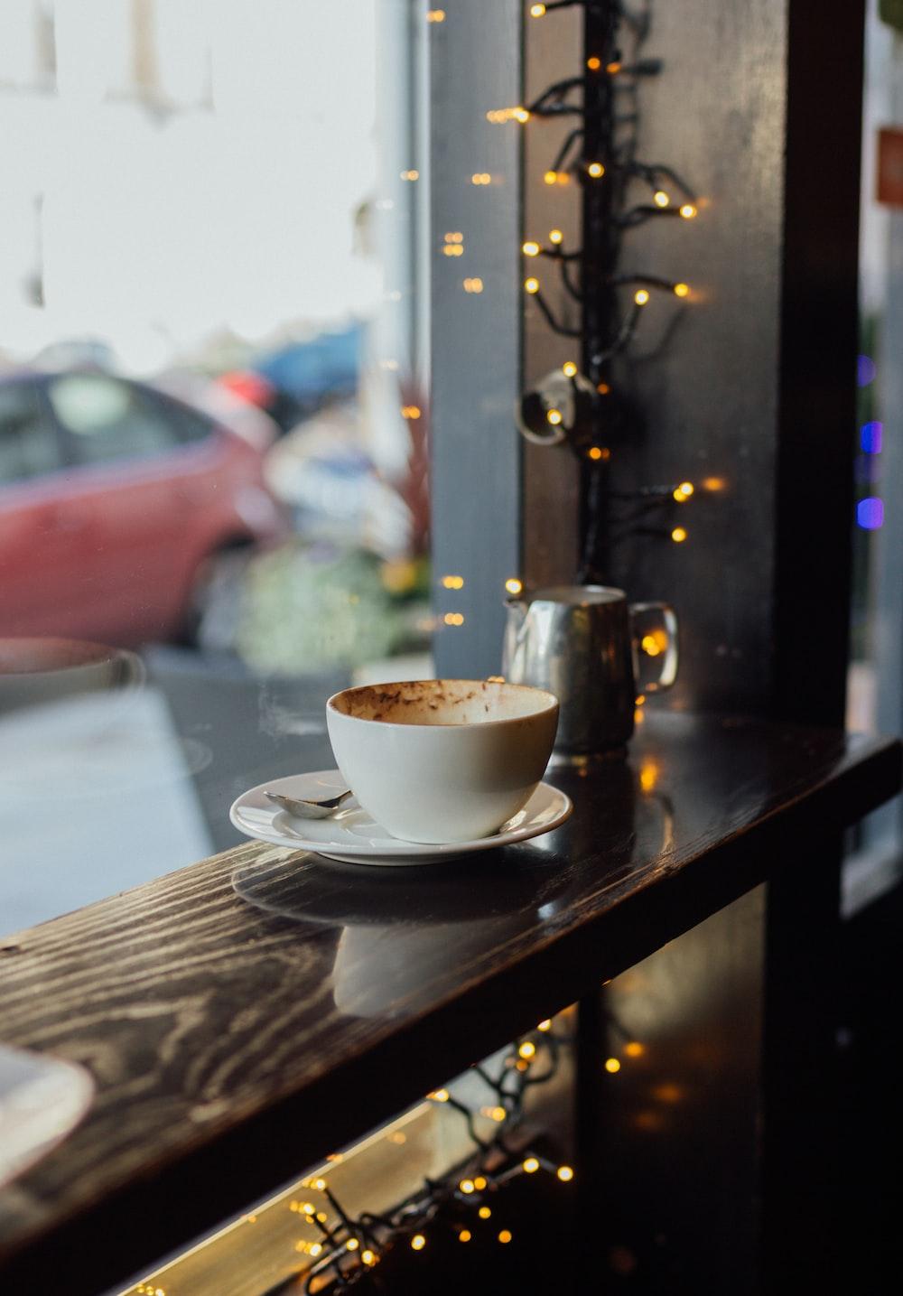 selective focus photography of coffee mug with saucer near window