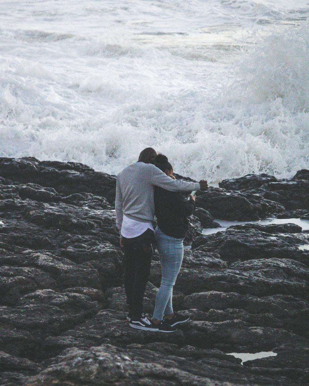 man and woman on rock near beach talking photo