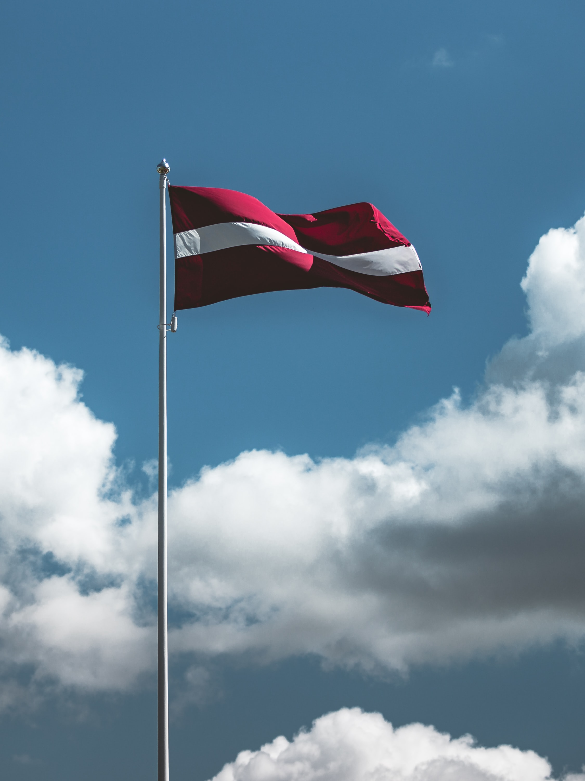 waving red and white striped flag on pole