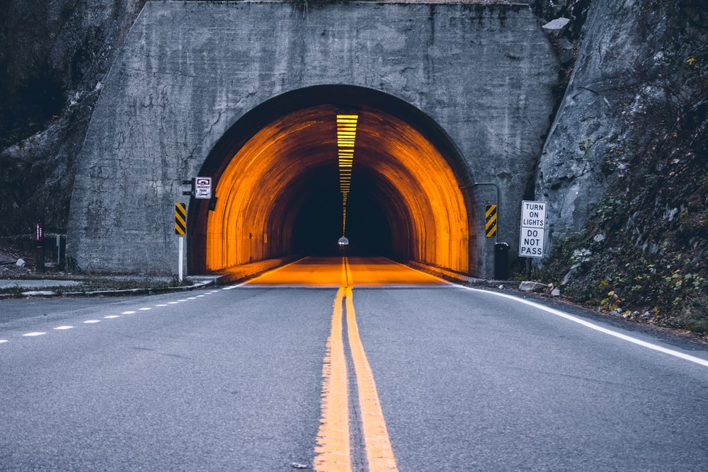 yellow-lighted arch tunnel road