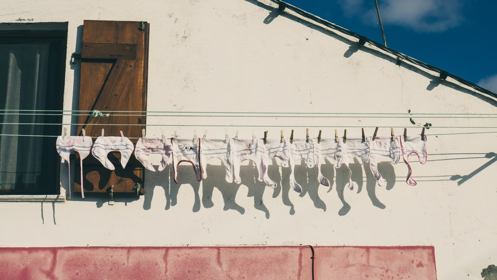 baby's white clothes hanged on white clothes rack