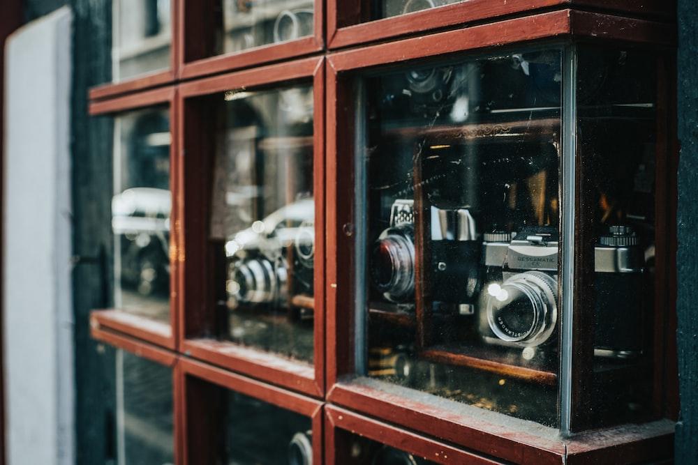 assorted cameras displayed inside glass cases