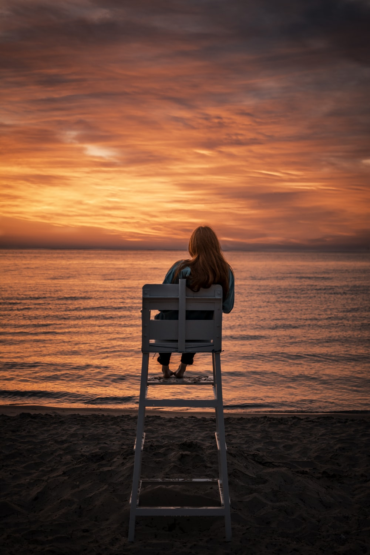 woman sitting on high chair facing seashore