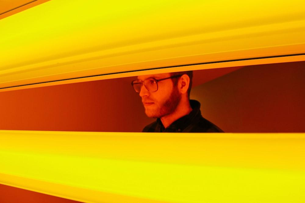 man in black shirt looking through yellow blinds