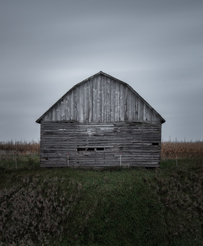 brown wooden barn near corn field