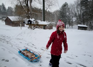 girl about to carry brown and blue toboggan