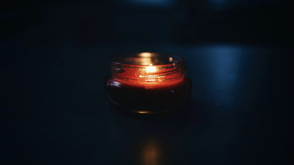 black and red votive candle with flame