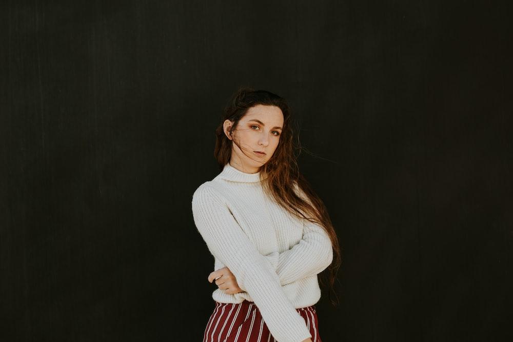 woman wearing white sweater making pose