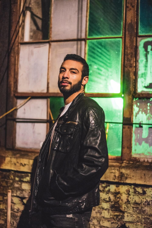 man wearing black leather jacket near window