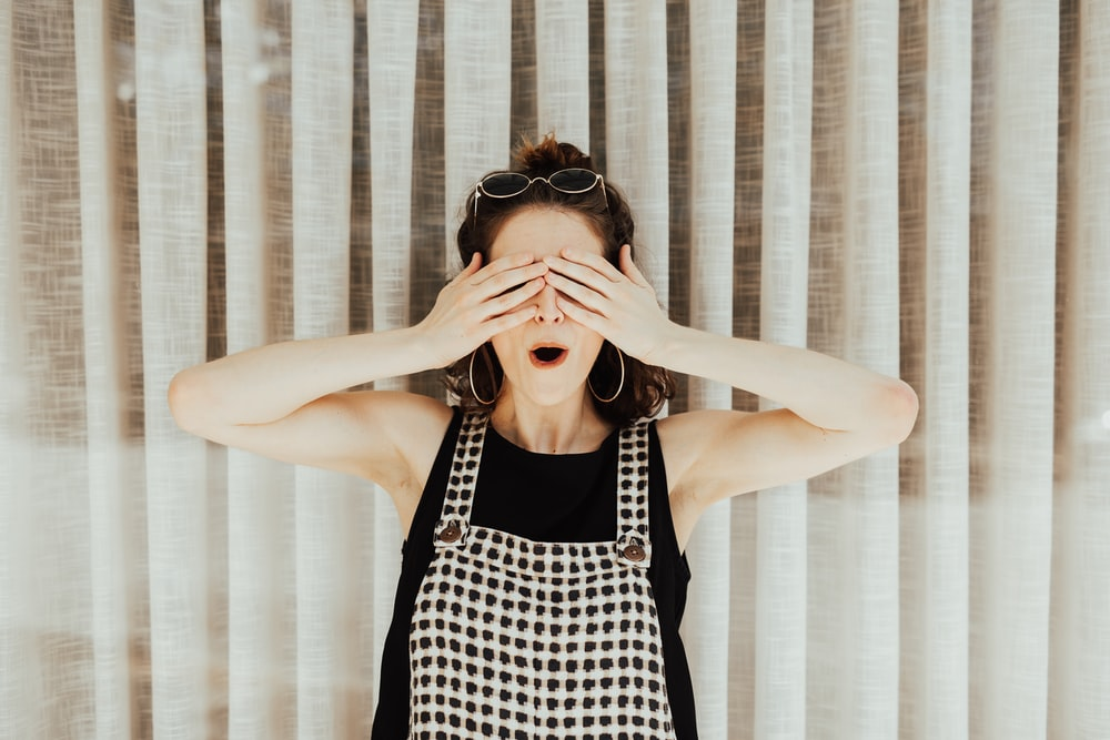 woman covering eyes with hand