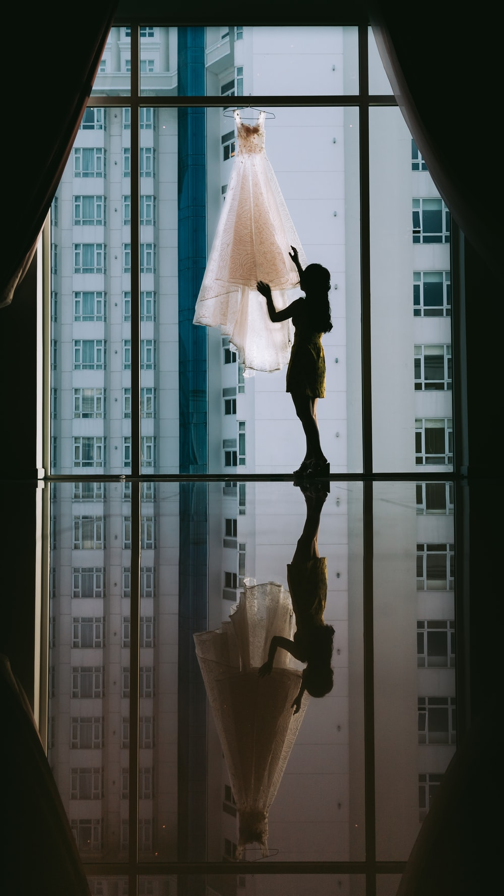 women's white gown hanged on clear glass window