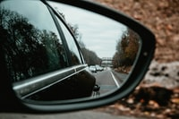 reflection of cars on asphalt road in side view mirror