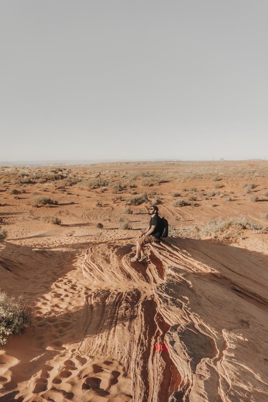 man sitting on brown ground