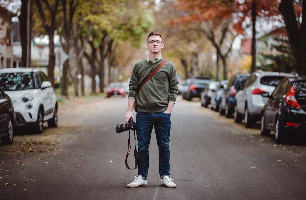 man standing in the middle of the road near parked cars holding DSLR camera