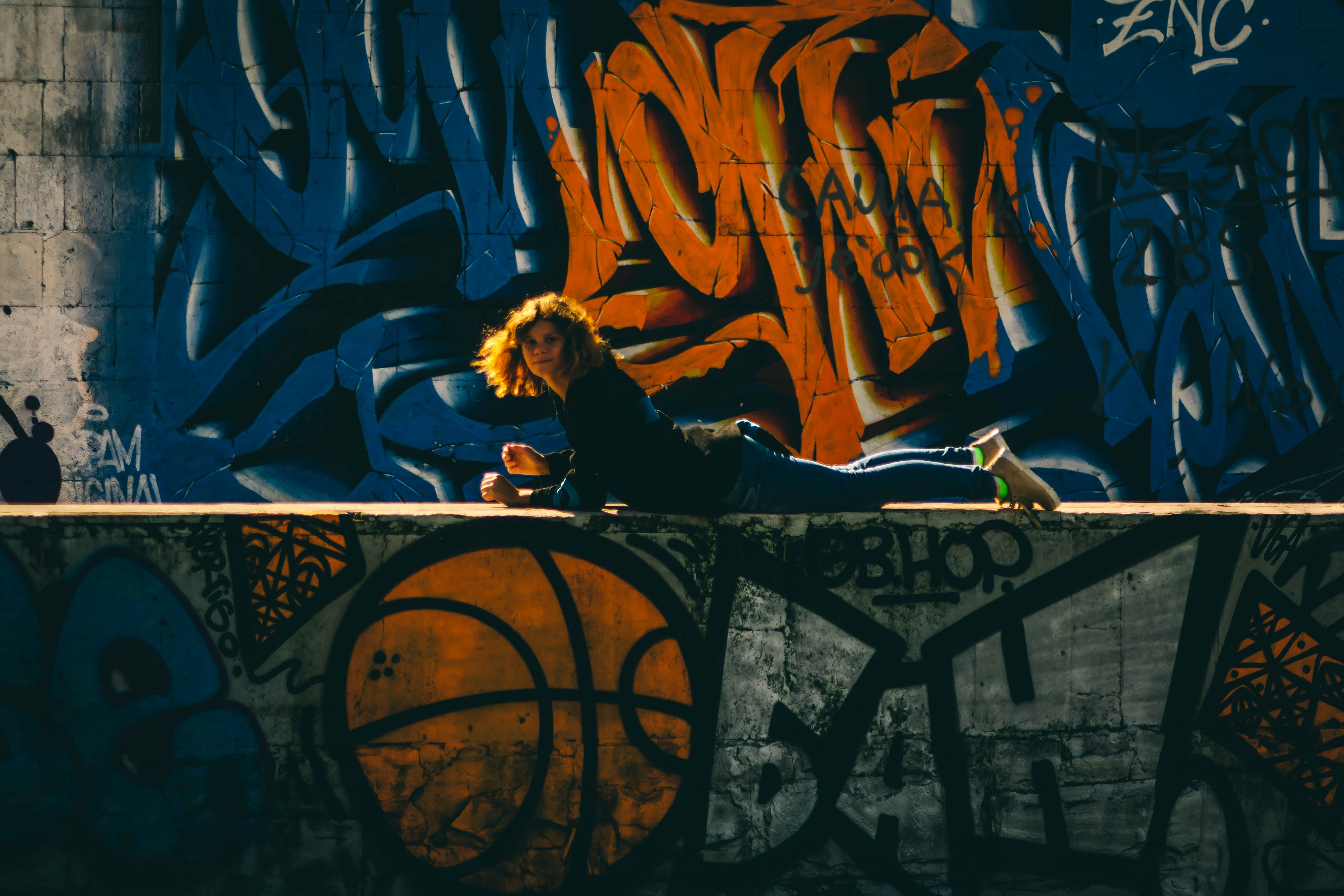 photography of woman lying down on graffiti painted wall