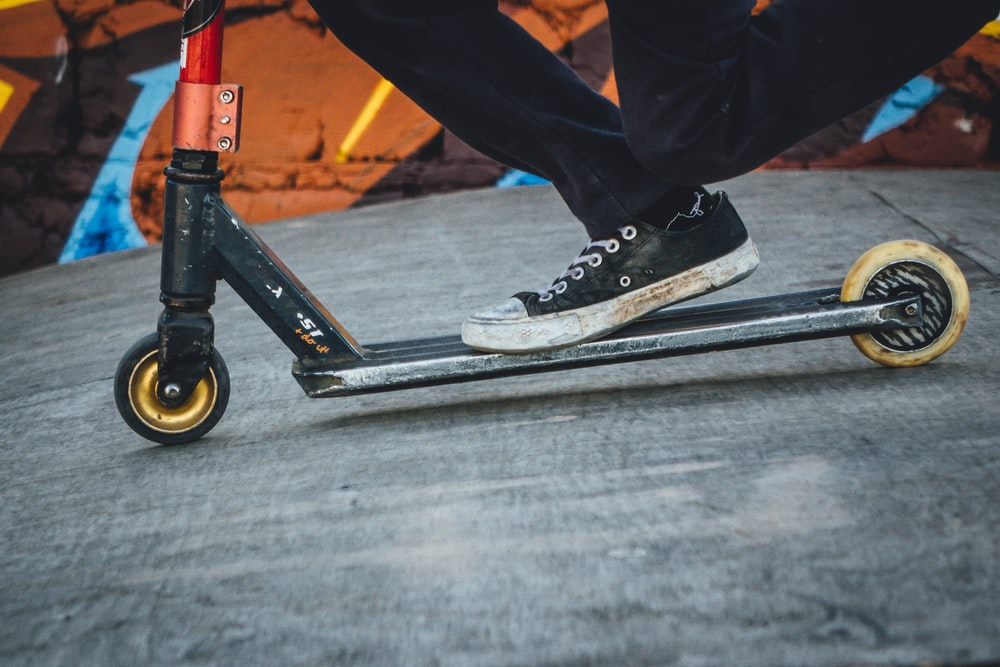 person riding gray and black kick scooter on gray concrete surface