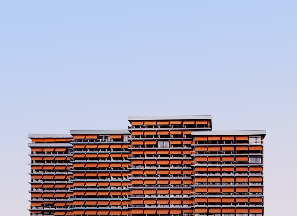 orange and white high-rise building under blue sky during daytime