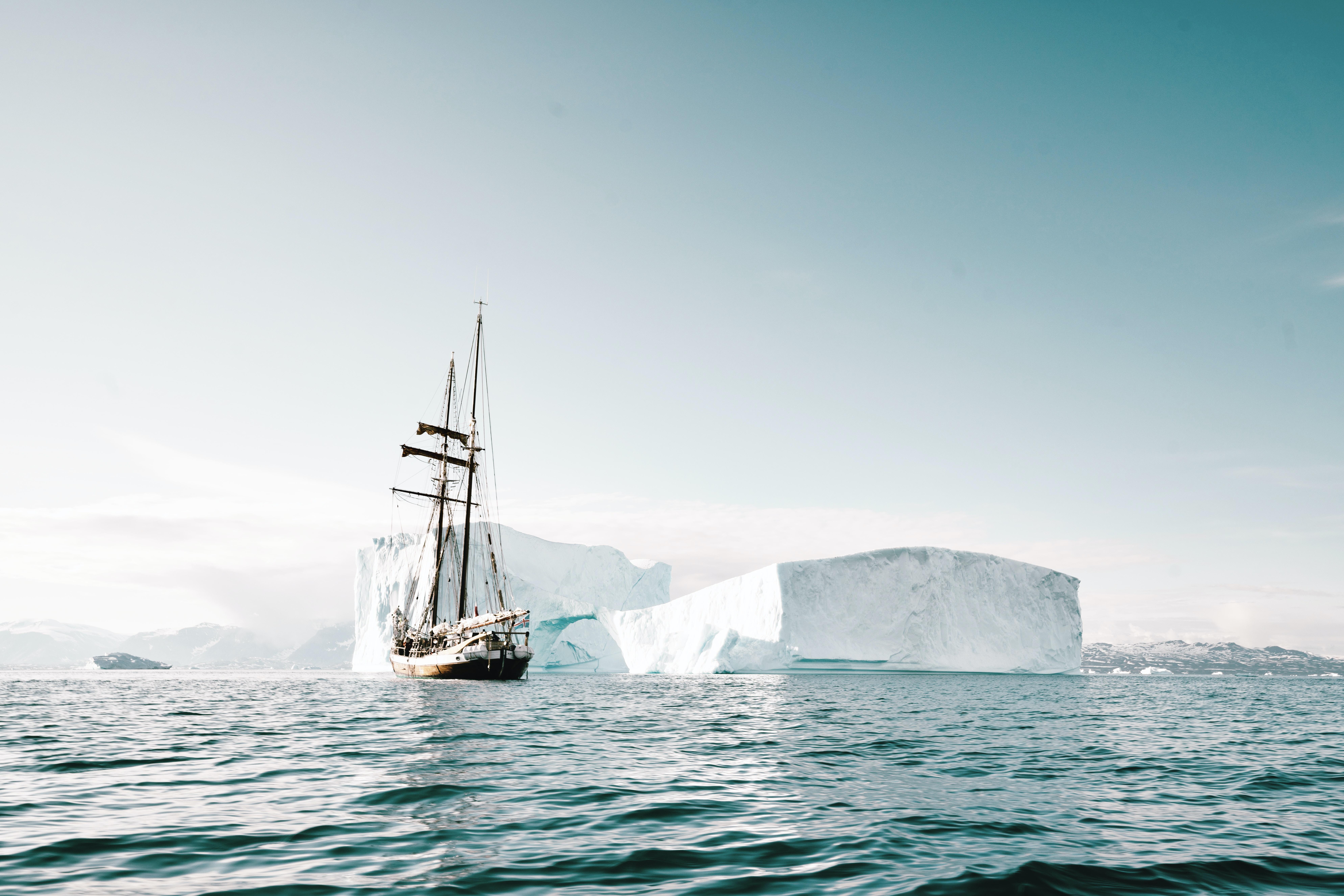 white sailing ship beside iceberg