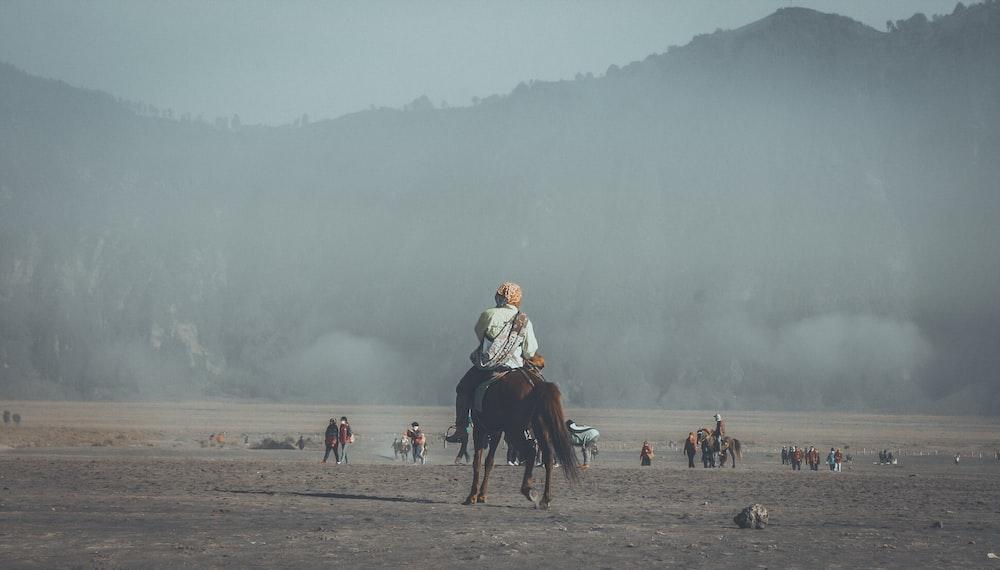 man riding horse far away from mountains