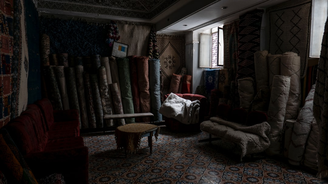An open windows lights the a dark and dusty room fool of carpets with a couch and a round table.