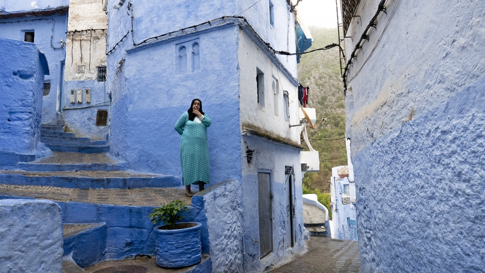 woman standing on stairs beside blue building
