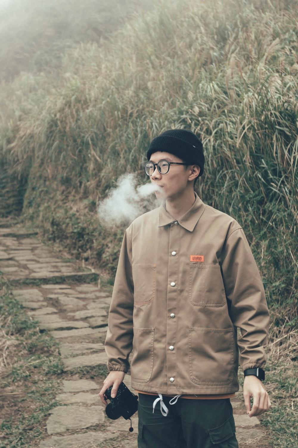 man standing on pathway while smoking