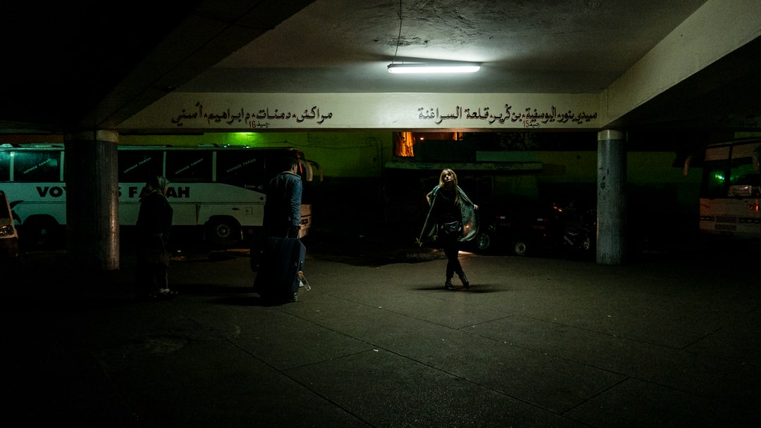 Girl with green scarf and black vest stands behind a light in a portico of a bus station. A weird green light illuminates the scene with two travellers walking on a side.