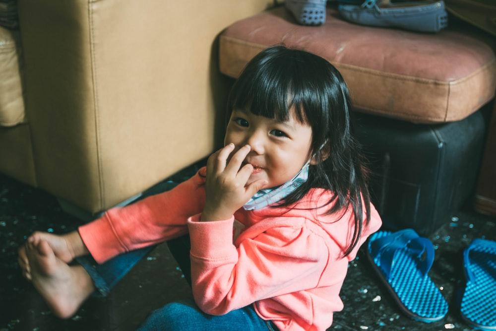 toddler girl biting her finger