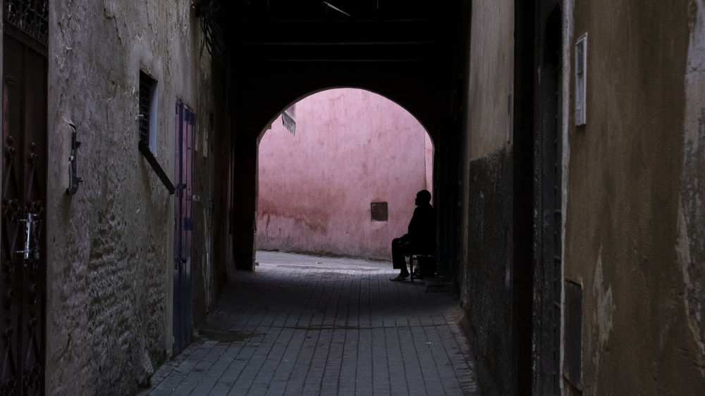person sitting at the end of the alley