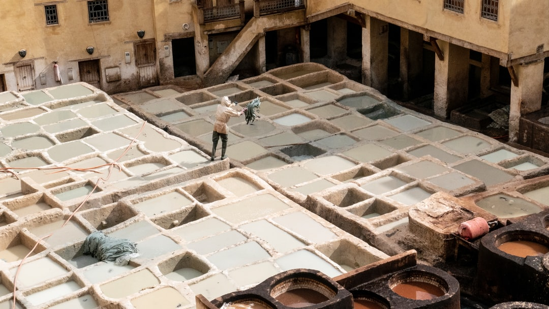 Man standing on into the tannery throwing leather into color sink
