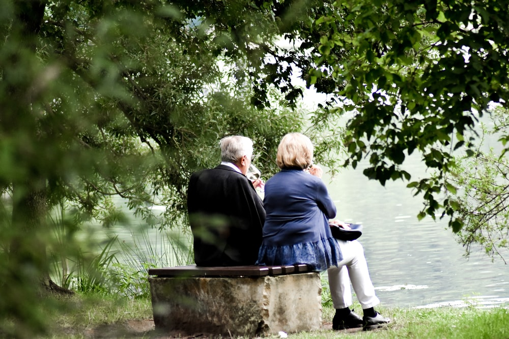 two people sitting on pavement facing on body of water