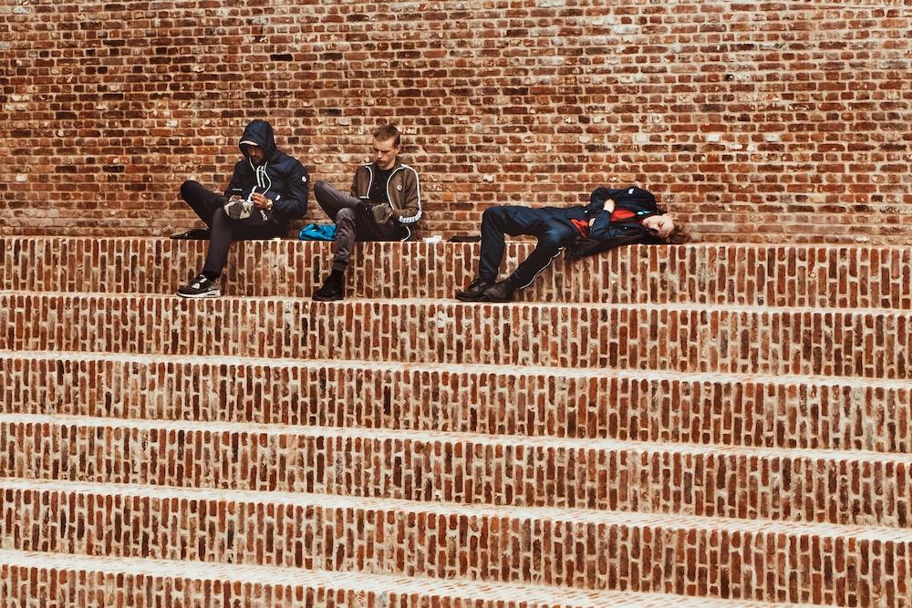 three men sitting on stair