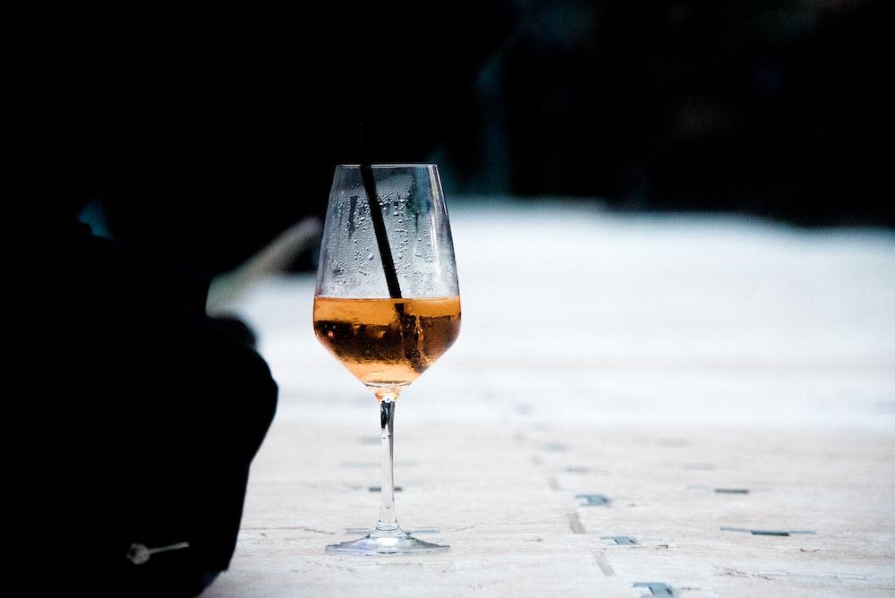 selective focus photography of half-empty wine glass on the floor