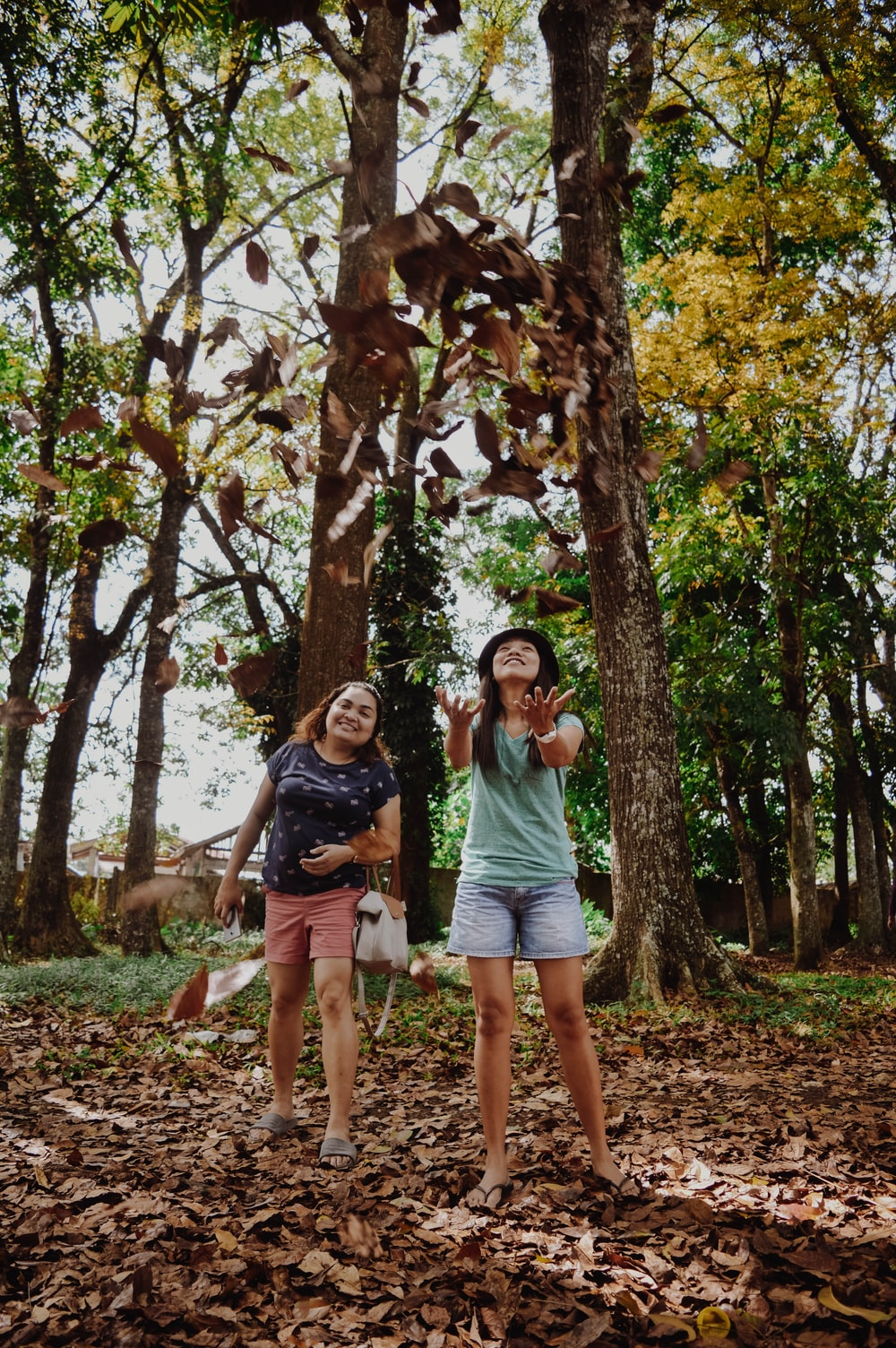 two woman standing near trees