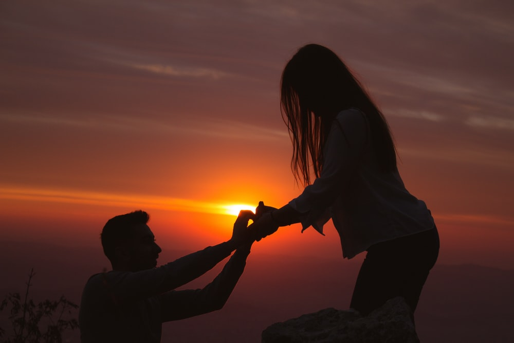 silhouette photography of man kneeling in front of woman