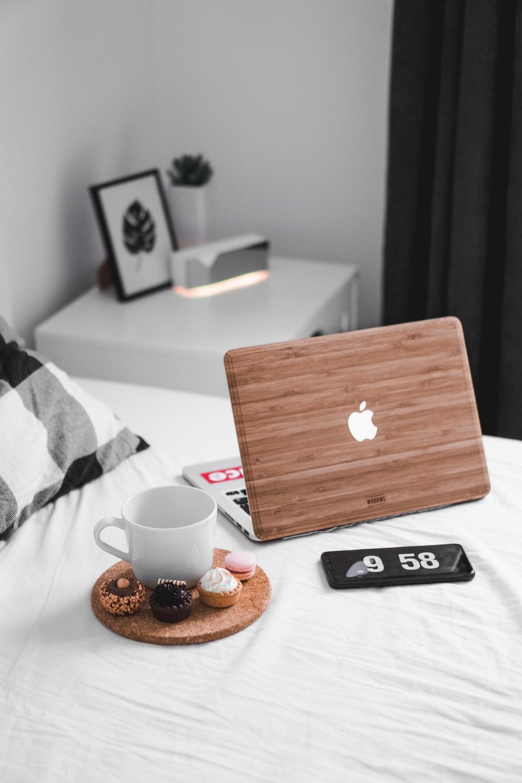MacBook beside white mug