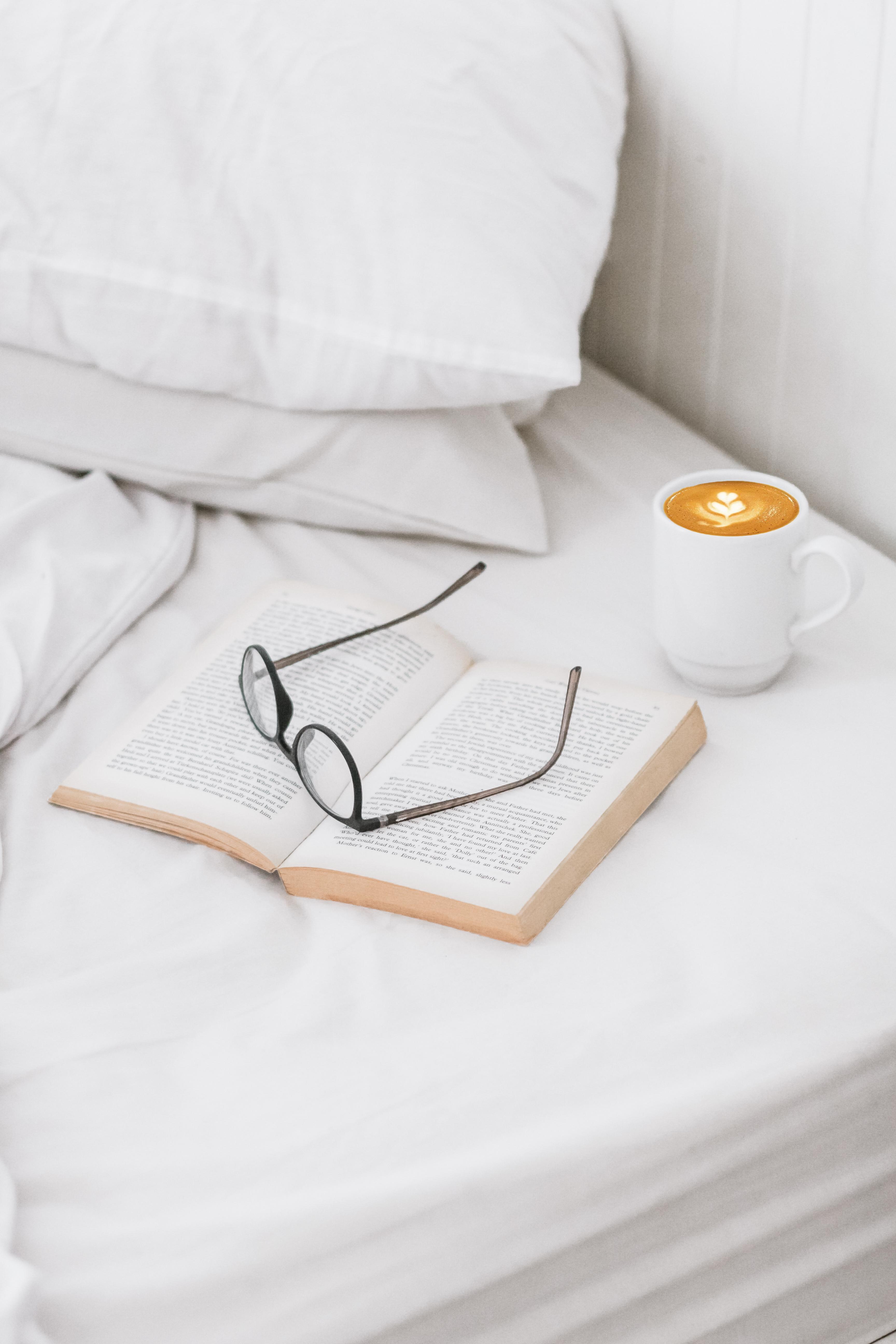coffee on ceramic mug, book, and eyeglass on bed
