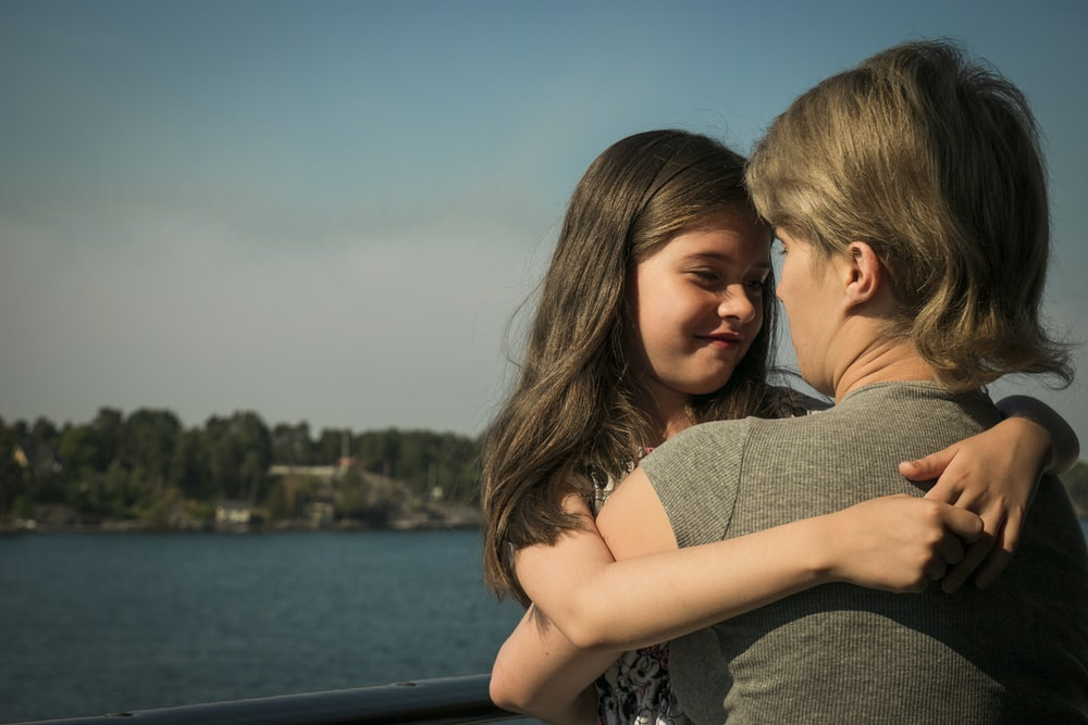 girl and mother hugging each other