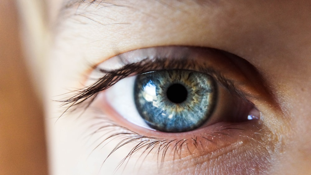person opening his right eye with blue iris