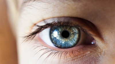 person opening his right eye with blue iris eye zoom background