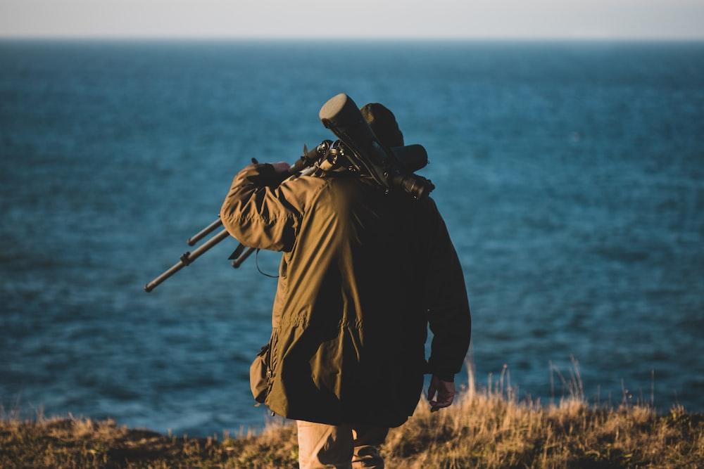 man wearing black jacket walking near the ocean