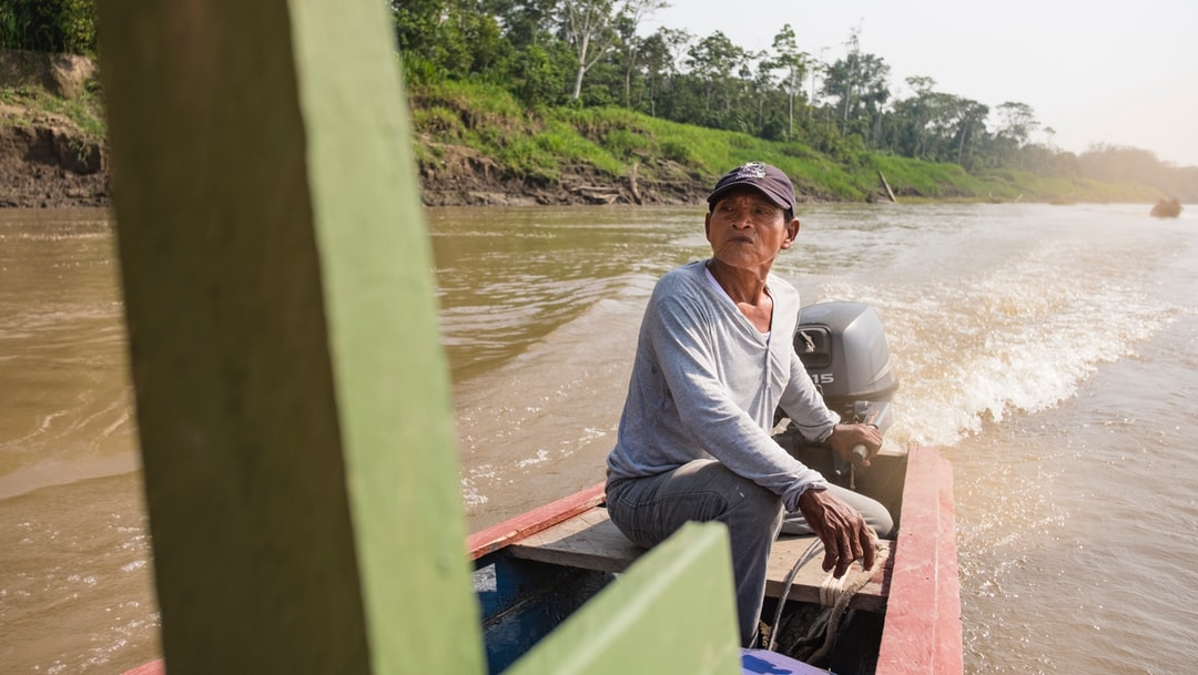 A man with his boat on a muddy river