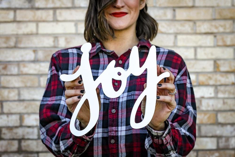 woman holding joy text